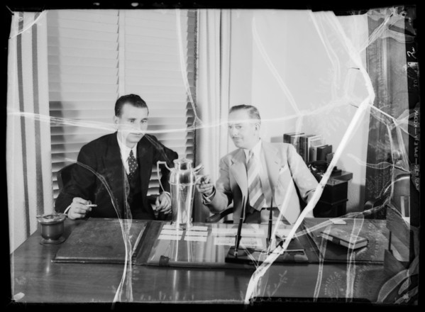 Two men at desk with golf trophy, Southern California, 1935