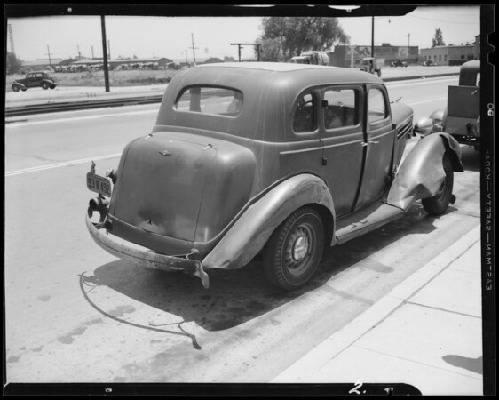 1937 Plymouth coupe, (assured), 1935 Dodge sedan, and skidmarks at 20th Street & Long Beach Avenue, Los Angeles, CA, 1940