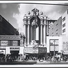 In Downtown Los Angeles, frontal view of the Los Angeles theatre showing Doself's and Berland's stores at left and Mode O' Day and Mayson stores at right
