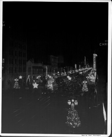 Hollywood Boulevard looking east from Highland Avenue, showing streetlamps decorated as Christmas trees lit during the night, ca.1938-1939