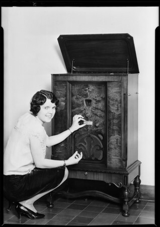 Girl putting plates on radio, Southern California, 1930