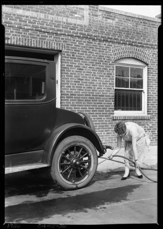 Girl with brush under the car, Southern California, 1926