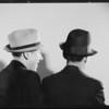 Men watching Wilbur Shaw shooting at tire, Southern California, 1934