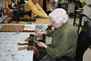 Maria is mixing three different shades of hair color on a 100 year old heckle. The end result will be one color. She's worked at Bob Kelly's shop for 50 years.