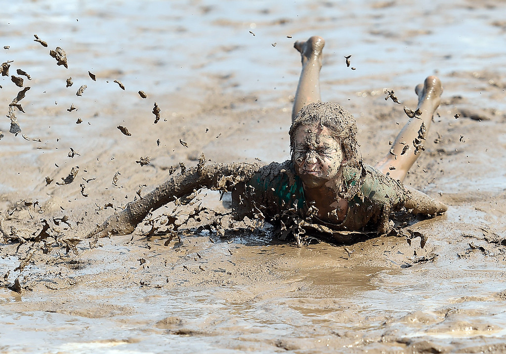 . Hailey Brewster, 11, slides through the mud on her stomach Tuesday , Aug. 7, 2018, during Wild and Crazy Kids Day at the Larimer County Fair at The Ranch in Loveland.  (Photo by Jenny Sparks/Loveland Reporter-Herald)