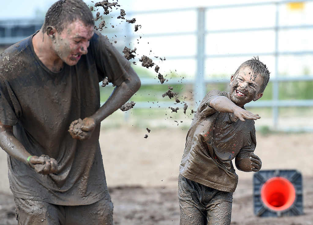 . Trinton Barker, 8, throws mud at Carl Allen, 17, while having a mud fight Tuesday , Aug. 7, 2018, during Wild and Crazy Kids Day at the Larimer County Fair at The Ranch in Loveland.  (Photo by Jenny Sparks/Loveland Reporter-Herald)