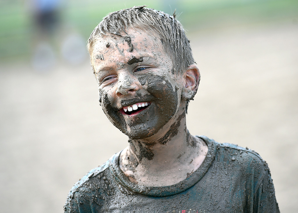 . Trinton Barker, 8, laughs while taking a break from playing in the mud Tuesday , Aug. 7, 2018, during Wild and Crazy Kids Day at the Larimer County Fair at The Ranch in Loveland.  (Photo by Jenny Sparks/Loveland Reporter-Herald)