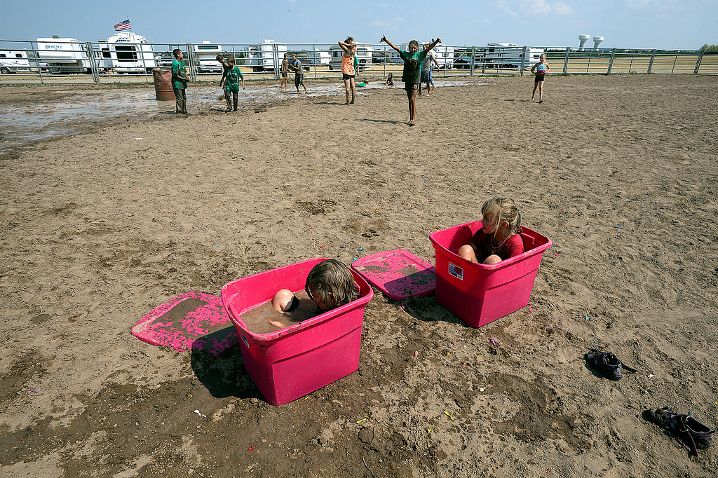. Bailey Hood, 6, left, and Kenzie Hogan, 6, right, sit in the water balloon bins to rinse some of the mud off of them Tuesday , Aug. 7, 2018, during Wild and Crazy Kids Day at the Larimer County Fair at The Ranch in Loveland.  (Photo by Jenny Sparks/Loveland Reporter-Herald)
