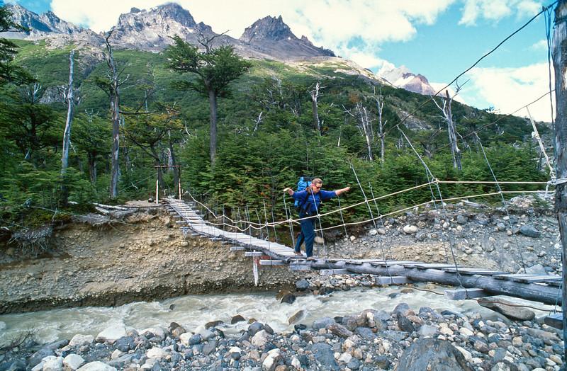Karen crosses a swing bridge. The Torres del Paine Circuit in the Torres del Paine National Park (Parque Nacional Torres del Paine), Chile.