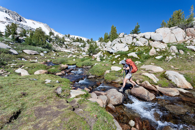 Karen crossing another stream while descending the south side of Donohue Pass. John Muir Trail, the Sierra Nevada Mountains in California, United States.