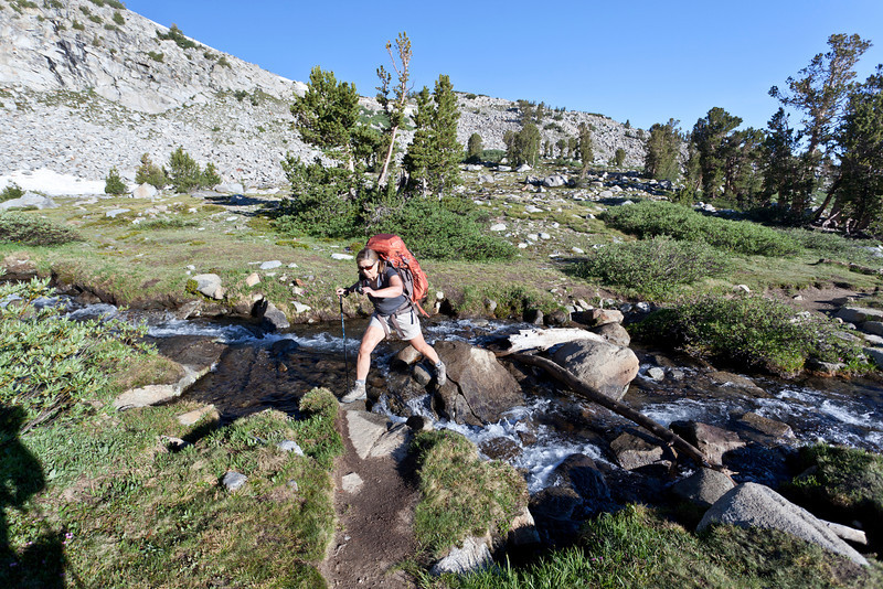 Karen crossing a stream on the climb up to Donohue Pass (11056 feet). John Muir Trail, the Sierra Nevada Mountains in California, United States.