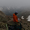 John checking the route as we down climbed. Windom's north ridge was straight down the right side of this image. Our campsites were just above the hood of his jacket.