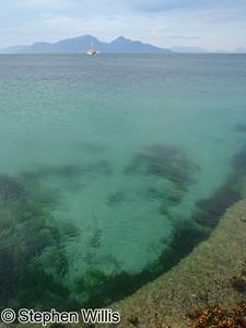 Eda sitting in clear Hebridean waters, Muck