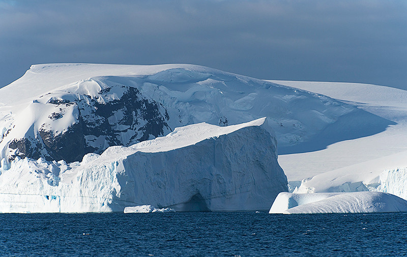 Tabular iceberg in center with domed iceberg on the right at Cierva Cove, located at the far northern end of Hughes Bay, at the northern end of the Gerlache Strait