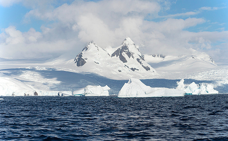 Cruising in a zodiac at Cierva Cove, located at the far northern end of Hughes Bay, at the northern end of the Gerlache Strait with Mt. Cornu (5623' (1714m). There is a large tabular iceberg in the foreground.
