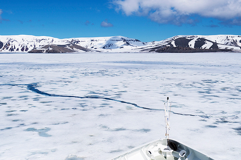 Port Foster, a harbor in the center of Deception Island, created from a volcanic calder, flooded by the sea, the entrance of which is Neptune's Bellows, a channel on the southeast side of Deception Island, heading for Telefon Bay with the remains of a winter ice shelf blocking its access.