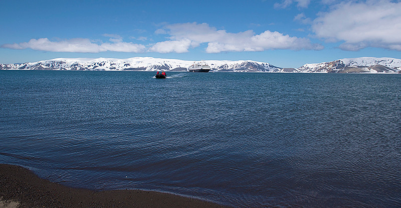 Zodiac coming in from the Silver Explorer at Telefon Bay, a small bay in the northwest side of Port Foster, Deception Island, in the South Shetland Islands, surmounted by Telefon Ridge, with the Stone Throw Ridge in the background