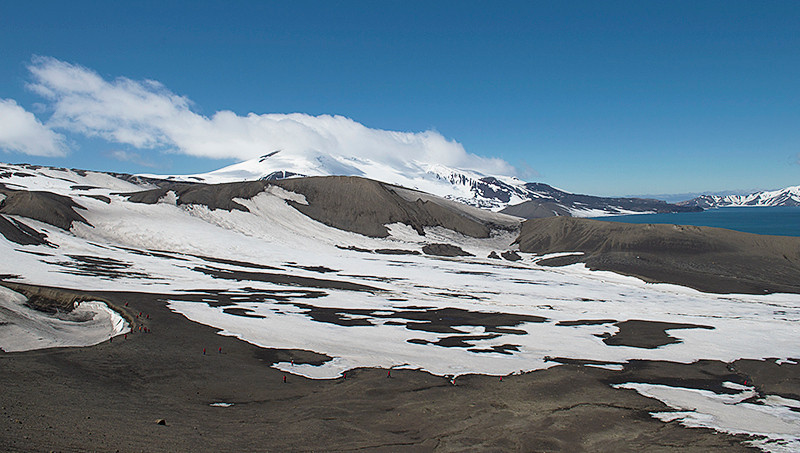 Looking out from the top of Laguna Hill, at Telefon Ridge at Telefon Bay, a small bay in the northwest side of Port Foster, Deception Island, in the South Shetland Islands toward Goddard Hill