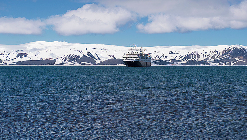 Silver Explorer at Telefon Bay, a small bay in the northwest side of Port Foster, Deception Island, in the South Shetland Islands, surmounted by Telefon Ridge, with the Stonethrow Ridge behind the Silver Explorer