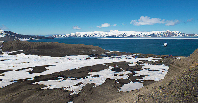 Looking out from the top of Laguna Hill, at Telefon Ridge at Telefon Bay, a small bay in the northwest side of Port Foster, Deception Island, in the South Shetland Islands toward the Silver Explorer in the bay