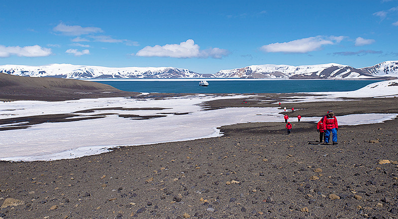 Hiking at Telefon Bay, a small bay in the northwest side of Port Foster, Deception Island, in the South Shetland Islands, surmounted by Telefon Ridge, looking back toward the Silver Explorer and Goddard Hill