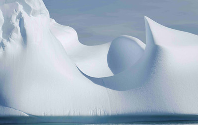 """The wind and sun contrive to melt the stranded bergs in various ways, producing this characteristic """"golf ball"""" surface pattern on the ice. At the bottom, the tide is contributing to the melting as well, with the effect that occasionally, the bergs suddenly tip over. A good reason not to get too close or go aboard!"""