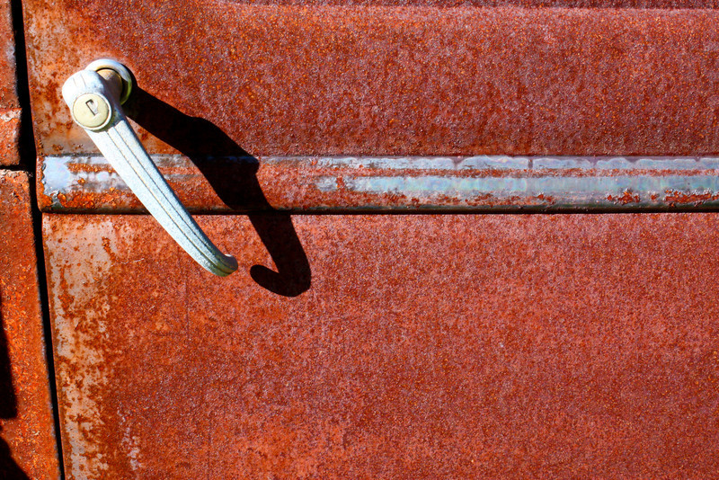 A rusted door of an old Ford pick up.  The afternoon sun lights it up.