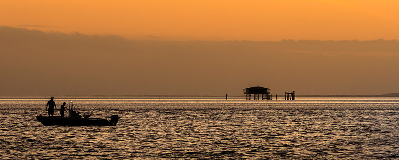 Fishermen and Stilthouse at sunset as seen from Bill Baggs State Park