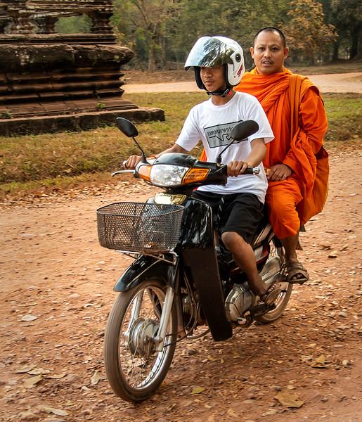 Senior Buddhist Monk Arriving at Angkor Wat via Motorcycle