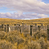 A lost graveyard on the lonely Montana praire.  The old wooden fences match the colors of the sagebrush and sand.  This is a melting of colors making an interesting image.  Someone took a great deal of time to build the enclosures to protect the graves from the winds of time.