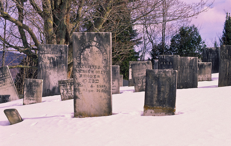 A long forgotten graveyard resting on a lonely hill.  The stones fit the coldness of the snow and frigid air.
