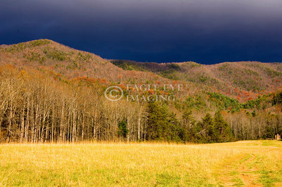 Sun shines in a valley as a thunderstorm moves over the mountains in Great Smoky Mountains National Park