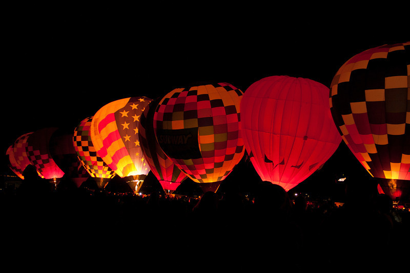 One balloon begins to rise in the darkness, then two, and three.  Soon the whole field is filled with color as the balloons fill with air.  The crowd is cheering.