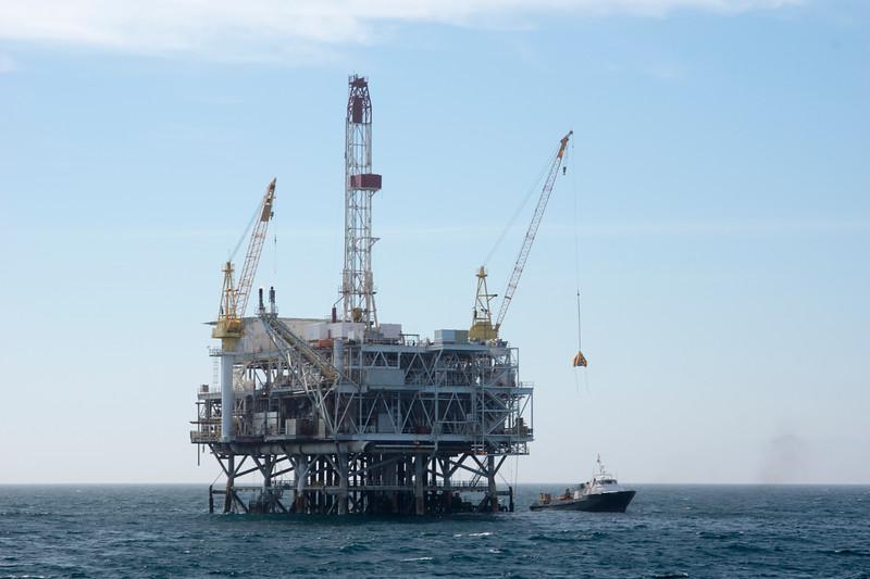 Oil platform resupplies using a crane.