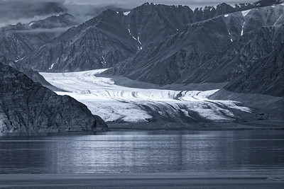 A receding glacier almost reaches Pond Inlet, with massive  moraines showing where the glacier used to be. Selenium tone.