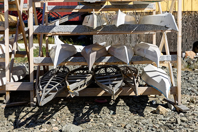 Traditional Greenland kayaks, tailored to each individual paddler, and usually hand made by the paddler, lie on the racks at the Sisimiut kayak club.