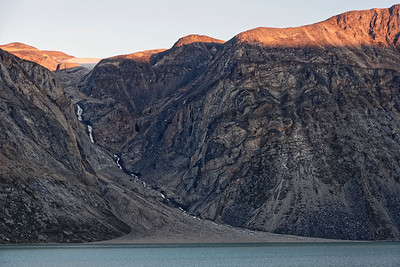 A meltwater channel in the side of the Kangaloussaq fjord has a steady stream coming down from the small icecap above.