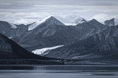 Moody landscape with ominous lenticular clouds at Pond Inlet, Baffin Island. Infrared shot with selenium tone.