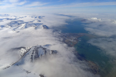 This is Svalbard taken from the plane window in late June 2013. It is a land of icy peaks, and warm (relatively) water from the Gulf Stream, a good recipe for fog. The plane flew over the fog with the peaks sticking up through it, and then a gap appeared with the fjord below, a pathway down to the airport at Longyearbyen. Lumix LX5 with a small reflection of the window in the lower right corner!