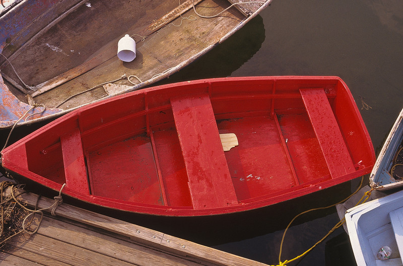A lovely red boat among many others dressed in drab brown or dirty white.