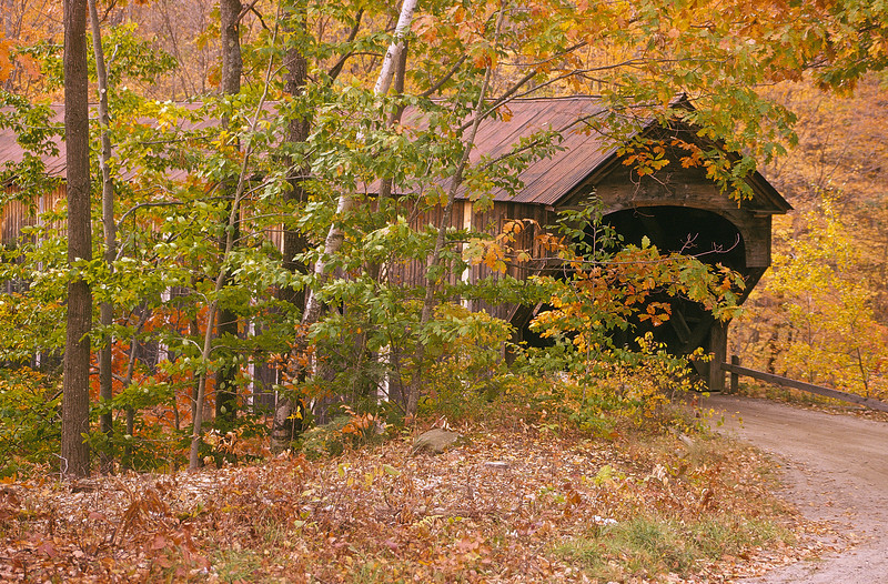 An old covered bridge found in Vermont.  It seems swallowed up by the Fall foliage and is found only by following a small dirt road.