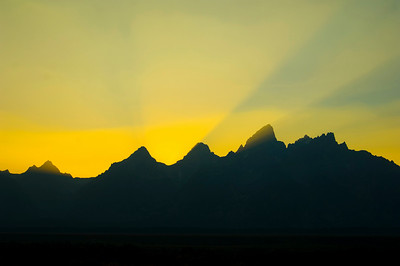 Sunbeams brighten the sky at sunset over the silhouetted mountains in Grand Teton National Park