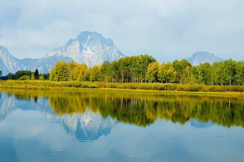 The reflection of the sky and mountains on a lake in Grand Teton National Park
