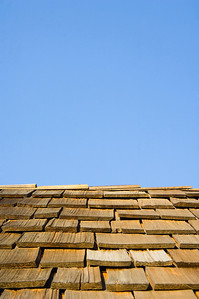 The wooden roof of an old church stands out against a blue sky