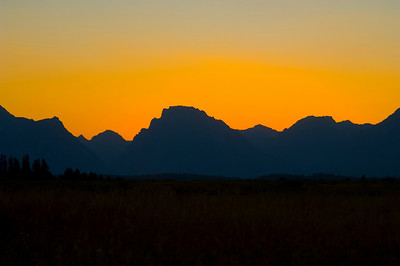 The orange glow of sunset silhouettes a western mountain range