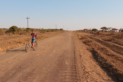 Zulu boy on bicycle, beaming from ear to ear, in the beautifully harsh Zululand landscape, full reds, browns and blues.  Rural Hluhluwe-iMfolozi KwaZulu-Natal