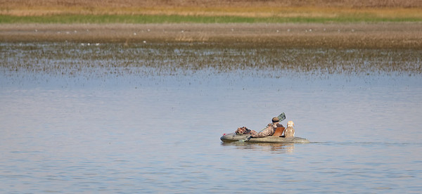 Hunter and dog in boat