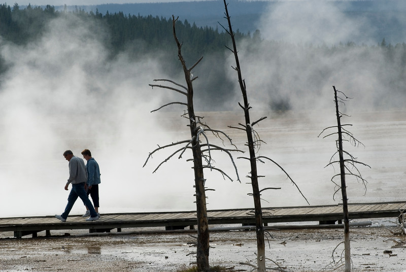 Tourists walk down a boardwalk in Yellowstone National Park - steaming geyser and hotsprings create a silhouette