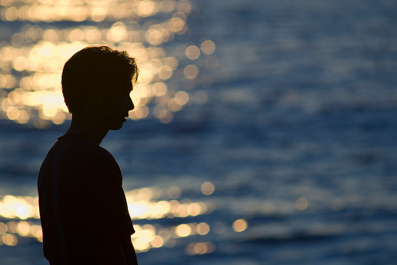 Ecotourism, a man's silhouette at sunrise or sunset along the ocean and coast