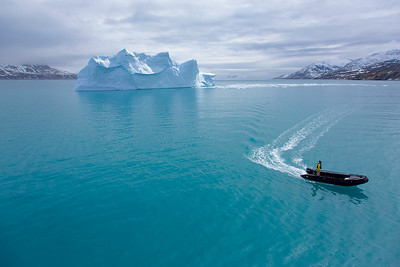 Expert guide and professional photographer Tom Murphy brings a Zodiac to the ship after checking out a floating iceberg.  South Georgia Island